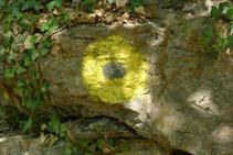 Cercle groc que hi ha pintat en un mur de pedra seca.