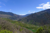 Mirada enrere: al fons veiem nevades les grans muntanyes de la vall Ferrera, entre les que destaca la característica piràmide del Monteixo (2.905m).