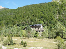 A l´altra banda hi destaca un bosc frondós i l´edifici del Parador del Monte Perdido.