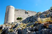 Torre circular sud-oest i muralla del castell del Montgrí. S´aprecien els merlets, les espitlleres i el matacà.