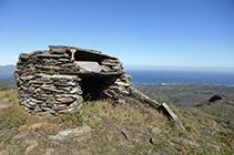 Just al costat de les antenes hi ha una cabana de pedra seca.