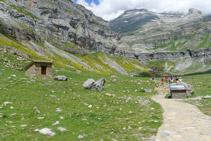 Cabana de pastors, panell explicatiu i, al fons, la capçalera de la vall.
