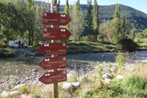 Senyalització vertical amb banderoles al costat del riu, eix vertebrador de la vall.