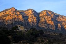 L´emblemàtica masia del Pujol de la Valldora i els cingles de Busa al darrera.