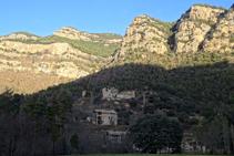 Les masies de Cal Guirre, Cal Teixidor i el Solà, amb les cingleres de Busa al fons.
