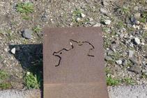 Placa d´acer corten que hi ha a la vora del camí amb S´Àliga dibuixada.