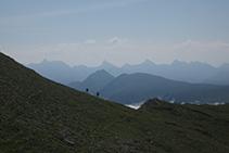 Dos excursionistes pujant cap al cim. Al fons: la Mesa de los Tres Reyes, el Petrechema, el Sobarcal, l´Acherito i el Chinebral de Gamueta.