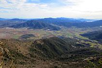 A l´E, les vistes a la Vall d´en Bas amb les serres del Corb i de Finestres.