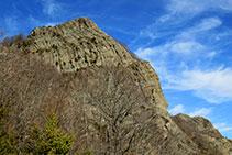 La cinglera del Puig dels Llops s´alça sobre el camí.