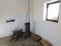 Interior del refugi Oller amb una estufa de llenya
