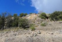 Tram rocós coronat per una paret amb una arcada de pedra.