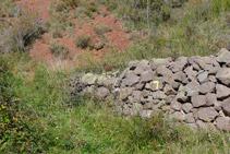 Muret de pedres amb el senyal groc del corriol que hem d´agafar.