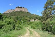 Pista de terra per on avancem i la roca del santuari de la Quar.