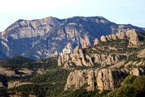 En primer terme hi veiem les roques montserratines de la serra dels Obacs. En segon terme hi tenim la salvatge serra d´Aubenç, amb lo Coscollet despuntant per sobre dels abismes. Intuïm el tall que fa el riu Segre entremig de les dues serres.