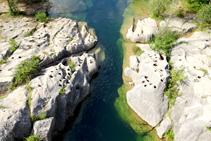 L´erosió de les aigües sobre el llit del riu.